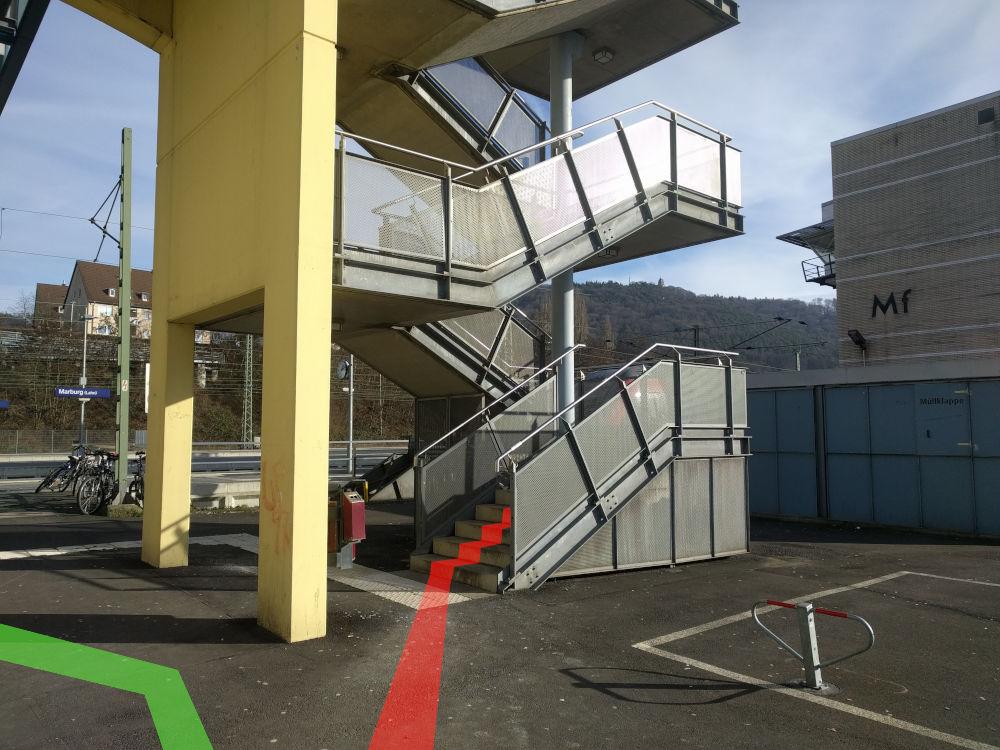 An der Südseite des Hauptbahnhofes Marburg gibt es eine Treppe, die zu einer Überführung über die Gleise führt (roter Pfad). Diese Treppe bitte hochsteigen. Ggfs. den Fahrstuhl nutzen, der von 6:30-1:30 Uhr in Betrieb ist (grüner Pfad).
